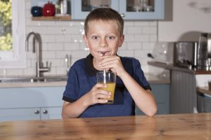 Boy drinking juice through metal straw