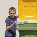 Boy placing egg carton into recycling bin
