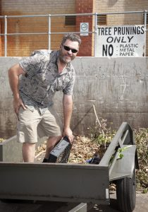 Man smiling while dropping off green waste