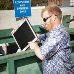 Man placing old computer into e-waste bin
