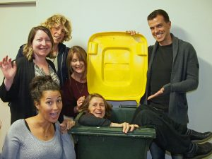 Group of smiling people with and inside a recycling bin