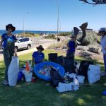 Smiling volunteers standing behind rubbish collected from beach clean up